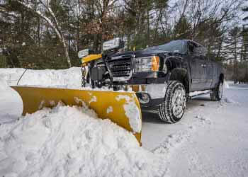 Image of snow plow removing snow from commercial parking lot.
