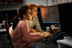 Two women examine data on a computer screen